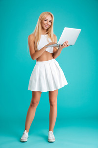 Full length portrait of a happy blonde woman standing and using laptop computer isolated on the blue background