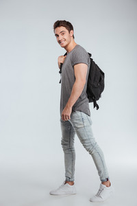 Full length portrait of a happy casual man with backpack standing isolated on a white background