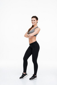 Full length portrait of a happy fitness woman standing with arms folded isolated on a white background