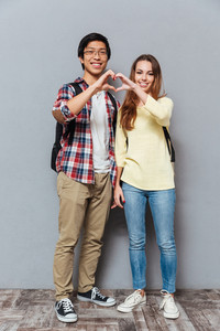 Full length portrait of a happy interracial student couple with backpacks showing heart gesture with hands isolated on the gray background