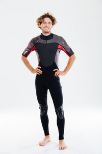 Full length portrait of a happy joyful sportsman in diving suit holding arms on hips over white background