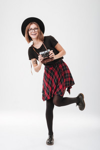 Full length portrait of a happy pretty girl in hat standing and holding retro camera isolated on the white background