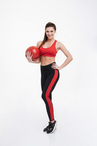 Full length portrait of a happy smiling fitness woman standing and holding red weight ball isolated on a white background