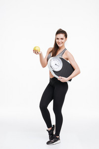 Full length portrait of a happy smiling fitness woman standing, holding an apple and scales isolated on a white background