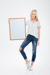 Full length portrait of a happy woman holding blank board isolated on a white background