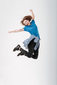 Full length portrait of a happy woman jumping with eyes closed isolated on a white background