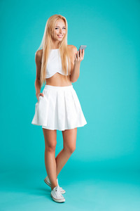 Full length portrait of a happy young blonde woman holding mobile phone and looking at camera isolated on the blue background