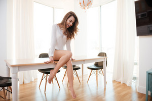 Full length portrait of a happy young woman in sweater sitting on table and laughing at home