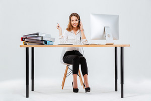 Full length portrait of a happy young woman working with computer in call center over white background