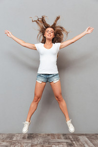 Full length portrait of a joyful woman jumping with hands up isolated on a gray background