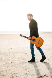 Full length portrait of a male musician walking on the beach with guitar