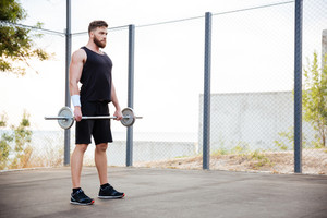 Full length portrait of a muscular fitness man doing heavy exercise using barbell outdoors
