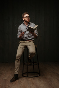Full length portrait of a pensive bearded man in eyeglasses sitting on chair and reading book isolated on a black wooden background
