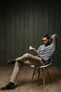 Full length portrait of a pensive bearded man reading book while sitting on chair isolated on a black wooden background