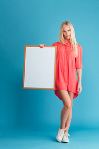 Full length portrait of a pretty woman holding blank board over blue background