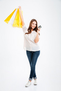 Full length portrait of a pretty young woman holding shopping bags and bank card isolated on a white background