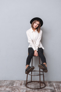 Full length portrait of a pretty young woman in hat looking away and sitting on chair isolated on the gray background