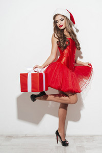 Full length portrait of a seductive beautiful woman in red santa claus outfit posing and holding gift box isolated on the white background