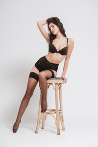 Full length portrait of a seductive sexy woman in lingerie with stockings sitting on chair and posing isolated on a white background