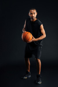 Full length portrait of a serious african sportsman playing basketball isolated on a black background