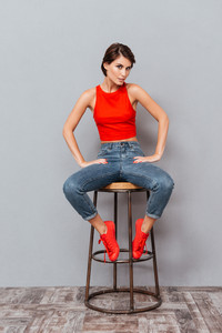 Full length portrait of a serious brunette girl sitting on chair isolated on the gray background