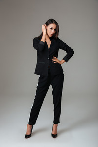 Full length portrait of a serious brunette woman in black suit standing and posing over gray background