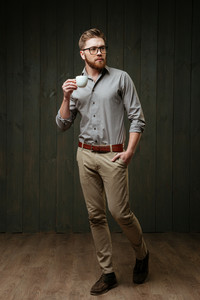 Full length portrait of a serious handsome man in eyeglasses holding cup of coffee and looking away isolated on a black wooden background