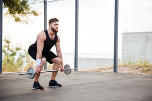 Full length portrait of a serious young bearded man athlete exercising and lifting barbell outdoors