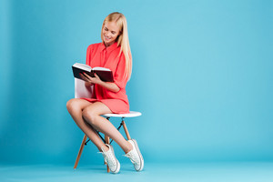 Full length portrait of a smart casual blonde woman in red dress reading book while sitting on chair isolated on the blue background