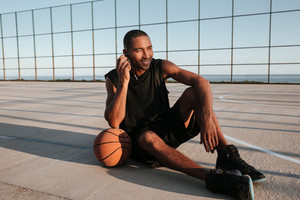 Full length portrait of a smiling african basketball player sitting at the playground and listening music with earphones
