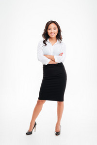 Full length portrait of a smiling asian businesswoman standing with arms folded isolated on a white background
