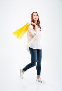 Full length portrait of a smiling attractive woman holding shopping bags isolated on a white background