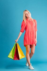 Full length portrait of a smiling attractive woman holding shopping bags over blue background