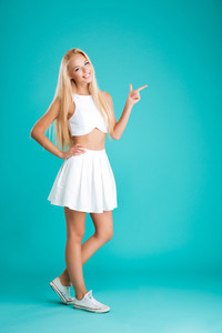 Full length portrait of a smiling attractive young woman pointing finger away isolated on the blue background