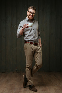 Full length portrait of a smiling bearded man in eyeglasses standing and holding cup of coffee isolated on a black wooden background