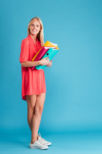 Full length portrait of a smiling blonde woman in red dress holding colorful folders over blue background
