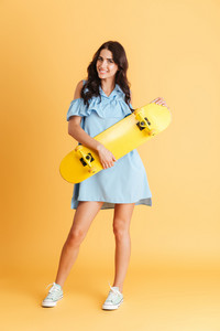 Full length portrait of a smiling brunette woman in blue dress holding yellow skateboard isolated on the orange background