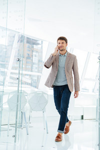 Full length portrait of a smiling casual businessman walking at the office building and talking on phone