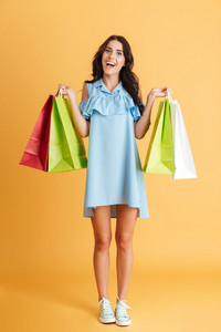 Full length portrait of a smiling casual girl holding shopping bags isolated on a orange background