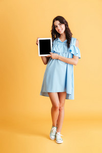 Full length portrait of a smiling casual woman showing blank tablet computer screen isolated on a orange background