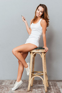 Full length portrait of a smiling casual woman sitting on the chair and using smartphone over gray backgorund