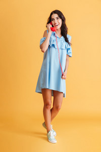 Full length portrait of a smiling happy brunette woman in blue dress talking on retro phone isolated on a orange background