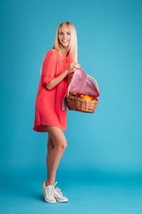 Full length portrait of a smiling happy girl in red dress showing basket with fruits isolated on a blue background
