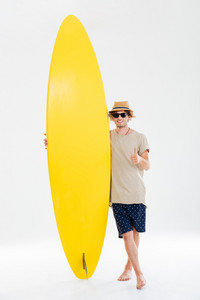 Full length portrait of a smiling happy man in sunglasses and hat showing thumbs up gesture and holding surfboard isolated on the white background