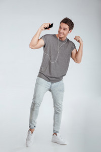 Full length portrait of a smiling happy man listening music with earphones and mobile phone isolated on the white background