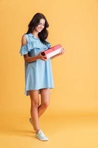 Full length portrait of a smiling pretty woman in dress holding gift box isolated on a orange background