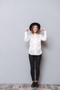 Full length portrait of a smiling pretty woman in hat standing and pointing up with both hands over gray background