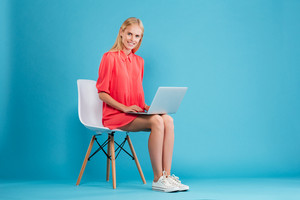 Full length portrait of a smiling pretty woman in red dress with laptop computer sitting on chair isolated on the blue background