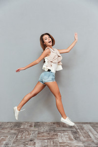 Full length portrait of a smiling pretty woman jumping isolated on a gray background
