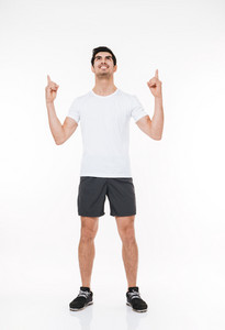 Full length portrait of a smiling sports man pointing fingers up over white background